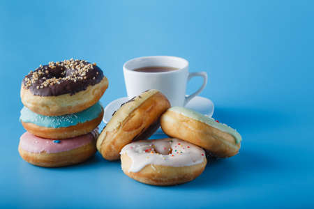 awry: Six donuts on blue shadeless background with cup of tea Stock Photo
