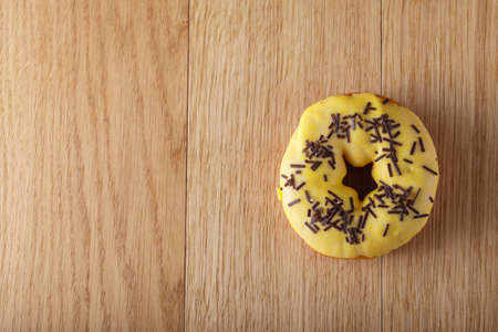 awry: Yellow donut on wood table