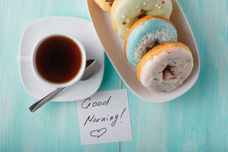 cup four: Four donuts on old wood table with cup and note Good morning
