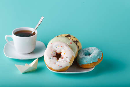 cup four: Four donuts on saucer with cup of tea and origami boat. Aquamarine background Stock Photo
