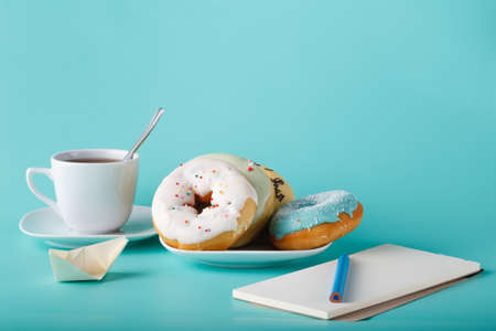 cup four: Four donuts on saucer with cup of tea. Aquamarine background with sketchbook