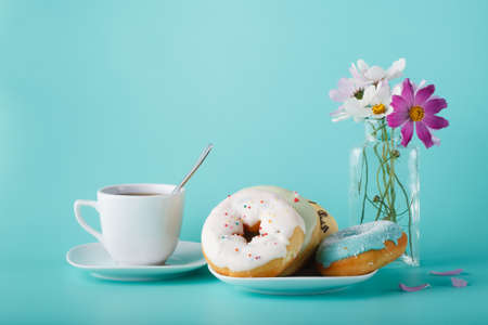 cup four: Four donuts on saucer with cup of tea. Aquamarine background and flowers