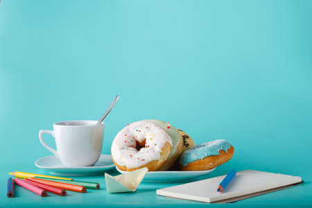 cup four: Four donuts on saucer with cup of tea. Aquamarine background with sketchbook and origami boat