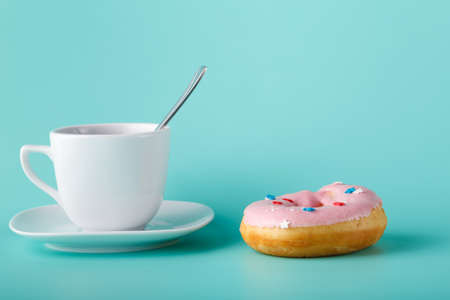 cup four: Four donuts on saucer with cup of tea. Aquamarine background