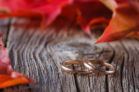 Wedding decoration. Red leaves on weathered table with wedding rings Standard-Bild