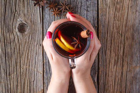 fall winter: Warm mulled wine in female hands, spices on weathered wooden table. Top view