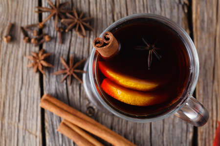 Mulled wine and spices on weathered wooden table. Selective focus