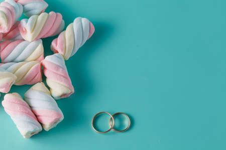 vibrant background: Twisted marshmallow on vibrant background. Wedding decoration golden rings Stock Photo