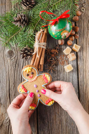 punch spice: Female hands puts gingerbread man on christmas spices, chinnamon, anise