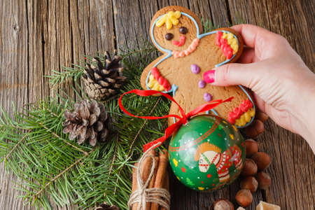 puts: Female hands puts gingerbread man on christmas spices, chinnamon, anise