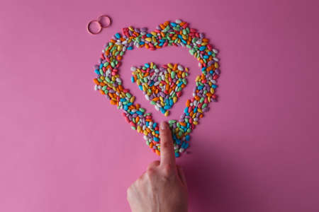 dragees: female finger painted colored heart from sweet dragees
