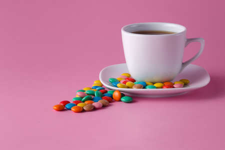 dragees: tea cup with colored sweet dragees on saucer