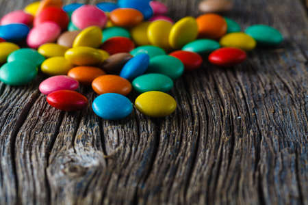 dragees: Colored sweet dragees on wooden textured table