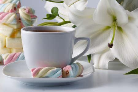 slowly: Concepto de desayuno. Taza de té, lirio blanco y malvaviscos de colores Foto de archivo
