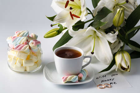 will you marry me: Morning tea cup with colored marshmallow white lily and note will you marry me Stock Photo