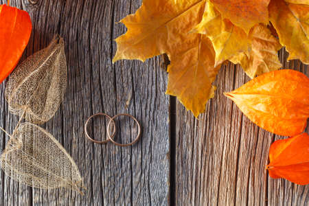 cape gooseberry: Fall wedding decoration. Dry cape gooseberry and two rings on rustic background Stock Photo