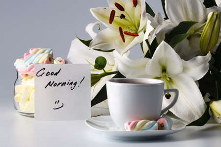 the good life: Breakfast concept. Cup of tea, white lily and note good morning