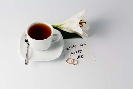 will you marry me: Breakfast concept. Cup of tea, white lily and note will you marry me Stock Photo