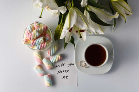 will you marry me: Breakfast concept. Cup of tea, white lily, colored marshmallow and note will you marry me
