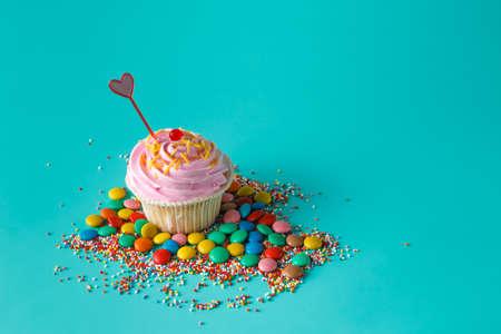 fun background: Birthday present. One cupcake on aquamarine background