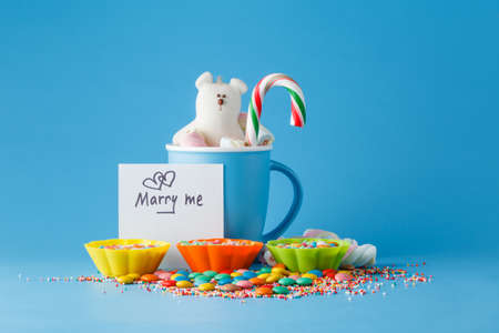 marry me: Kid decoration. Colored candy and mug with message marry me