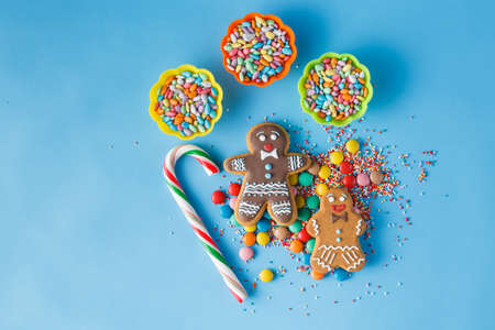 brigth: Two gingerbread man on blue background with striped stick