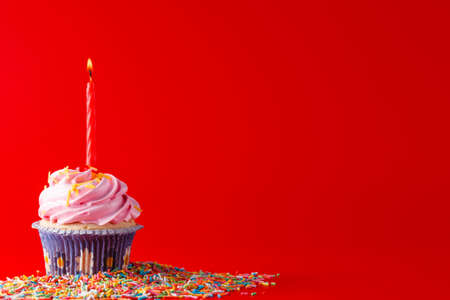 brigth: Kid birthday small gift. Cupcake with candle on brigth red background