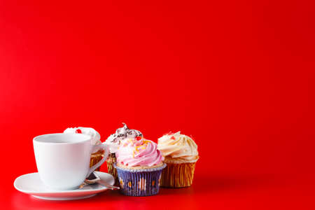 brigth: Sweet decoration. Cupcake with tea cup on brigth red background with copyspace