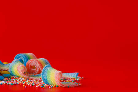brigth: Decoration concept. Colored sweet ribbon on brigth red background