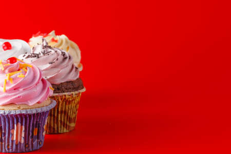 brigth: Colored cupcake with tea cup on brigth red background Stock Photo