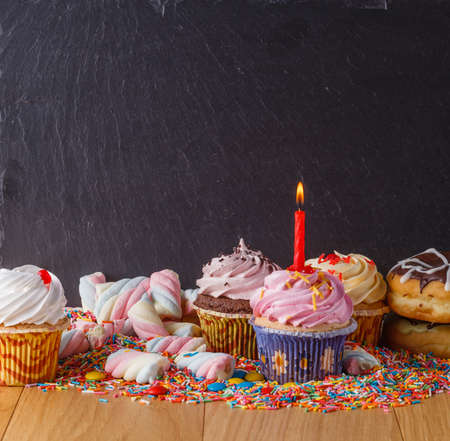 Sweets with copy space on black slate background. Donuts and cupcakes