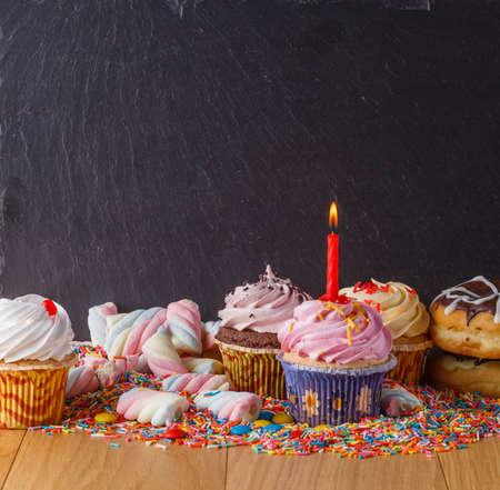 auguri di buon compleanno: Dolci con copia spazio su nero sfondo di ardesia. Donuts e cupcakes