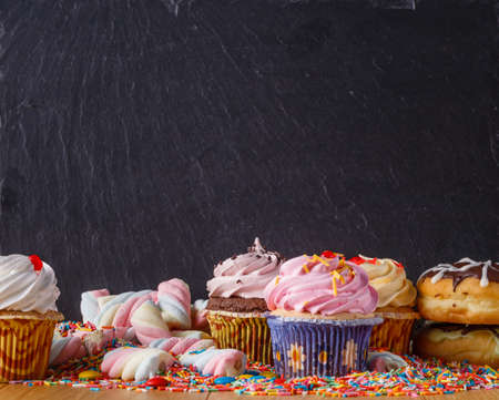 cupcakes: Sweets with copy space on black slate background. Donuts and cupcakes