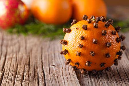 orange peel clove: Christmas decoration. Tangerine on rustic wood backgound