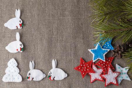coarse: Christmas frame concept. Soft felt figures on coarse woven
