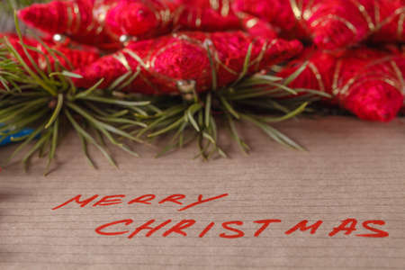 crafted: Text merry christmas on crafted papper and evergreen in background