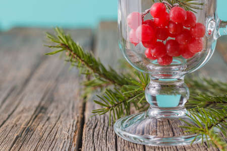 sooth: Frozen viburnum berry on rustic wooden background with pine