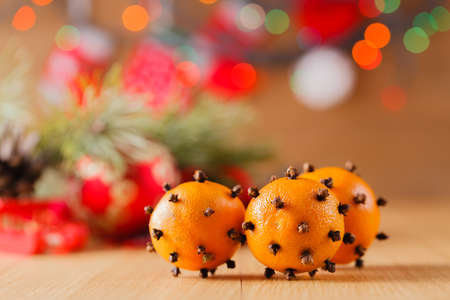 holiday lights display: New year decoration on table with Christmas tree garland and mandarines