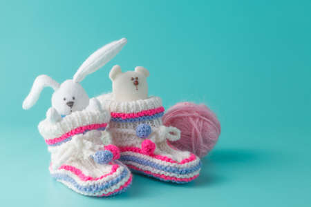 fondo para bebe: Concepto de anuncio de reci�n nacido. Botines de punto en el fondo de color aguamarina Foto de archivo