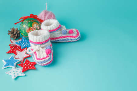 place for children: Newborn first christmas celebration. Knitted booties on aquamarine background and christmas decor Stock Photo