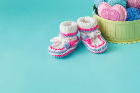 aquamarine: Newborn announcement concept. Knitted booties on aquamarine background with yarn clew