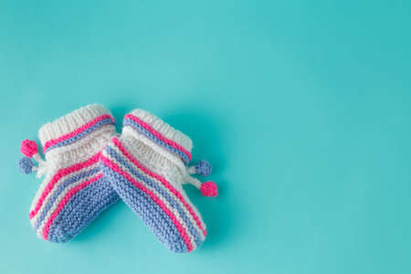 booties: Newborn announcement concept. Knitted booties on aquamarine background