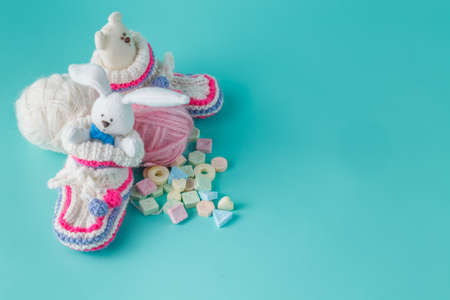 booties: Newborn announcement concept. Knitted booties on aquamarine background with sweets Stock Photo