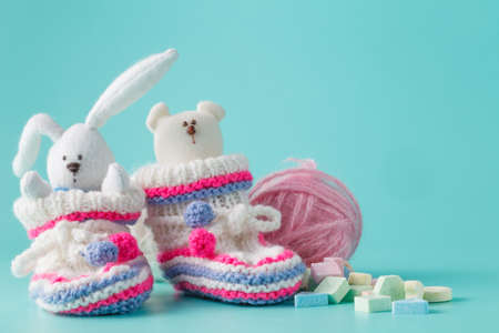fondo para bebe: Newborn announcement concept. Knitted booties on aquamarine background with sweets Foto de archivo