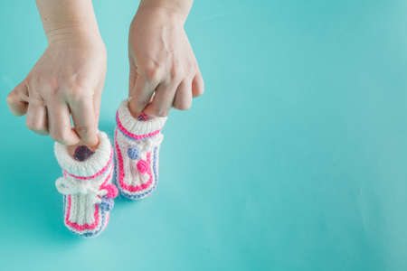 booties: Newborn concept. Female hands holding tiny knitted booties
