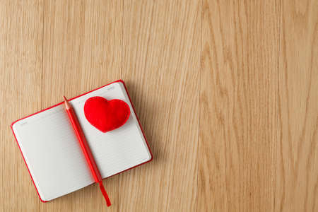 open diary: Soft red heart on wood table with open diary