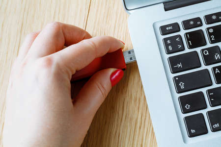 pendrive: Close up of a woman hand plugging a red pendrive on a laptop
