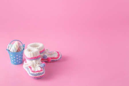 foot wear: Newborn invitation concept. Small foot wear with toy on pink background