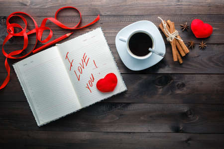 love message: Evening coffee dream. Dairy and pencil with love phrase on table