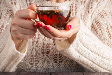 openwork: Female in white openwork pullover hold cup of herbal tea